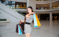 A young woman shopping in mall carrying bags and smiling Royalty Free Stock Photography