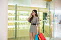 Young woman shopping in mall carrying bags and smiling Royalty Free Stock Photo