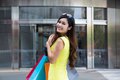 Young woman shopping in mall carrying bags and smiling Royalty Free Stock Image