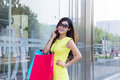 Young woman shopping in mall carrying bags and smiling Royalty Free Stock Photos
