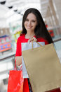Young woman shopping in mall red dress and gift bags Stock Images