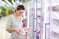 Young woman shopping for meat in a grocery store color toned image Stock Photography