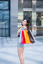 Young woman shopping outside the mall carrying bags and smiling Stock Photos