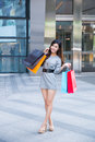 Young woman shopping outside the mall carrying bags and smiling Royalty Free Stock Images