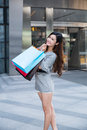 Young woman shopping outside the mall carrying bags and smiling Royalty Free Stock Photos
