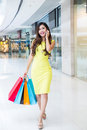 Young woman shopping phoning in mall carrying bags and smiling Royalty Free Stock Photos