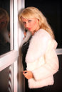 Young woman in short fur coat portrait of the a white near a window Royalty Free Stock Images
