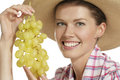 Young woman showing a bunch of grapes Stock Photo