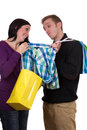 Young woman showing her friend a shirt while shopping women with bags isolated on white background Stock Images