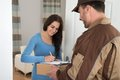 Young woman signing while receiving courier from delivery man at home Royalty Free Stock Image