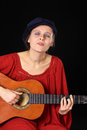 Young woman singing and playing the guitar caucasian with eyes closed selective focus focus on face Stock Photo