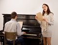 Young woman singing a solo song women standing alongside men playing an upright piano with obvious enjoyment Royalty Free Stock Photos