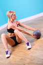 Young woman sit up with ball
