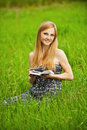 Young  woman sits on grass Stock Photography