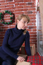 A young woman sits near a window. Christmas Royalty Free Stock Photo
