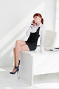 The young woman sits on a table at office Royalty Free Stock Photo