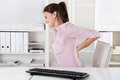Young woman sitting with backache in the office rose blouse Stock Photo
