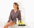 Young woman sitting in bathroom with bath cosmetics Royalty Free Stock Photo