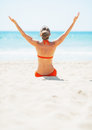 Young woman sitting on beach and rejoicing rear view in swimsuit sandy Royalty Free Stock Photo