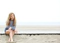 Young woman sitting at the beach thinking Royalty Free Stock Photo