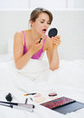 Young woman sitting in bed and applying makeup Stock Photos