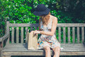 Young woman sitting on bench with paper bag Royalty Free Stock Photo