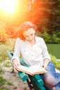 Young woman sitting on the bench and reading book Royalty Free Stock Photo