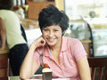 Young woman sitting at cafe table with dessert smiling portrait women Royalty Free Stock Images
