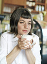 Young woman sitting at cafe table holding mug of coffee daydreaming close up Royalty Free Stock Photo