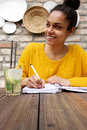 Young woman sitting at cafe and writing notes Royalty Free Stock Photo