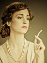 Young woman sitting with cigarette with long ash looking away holding a that is overly ready to Royalty Free Stock Images