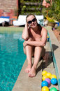 Young woman sitting close to swimming pool happy Royalty Free Stock Photography
