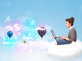 Young woman sitting in cloud with laptop pretty balloons and letters concept Royalty Free Stock Image