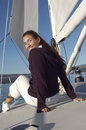 Young woman sitting on deck of sailboat portrait a happy women a Royalty Free Stock Image
