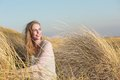 Young woman sitting in the dunes with long grass horizontal portrait of a Royalty Free Stock Image