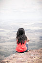 Young woman sitting at edge of cliff Royalty Free Stock Photo