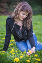 Young woman sitting in a field of dandelion flowers Royalty Free Stock Photo