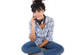 Young woman sitting on the floor with headphones calling someone white background Royalty Free Stock Photography
