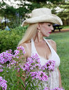 Young woman sitting by flowers pretty wearing cowgirl hat outdoors garden Stock Photo