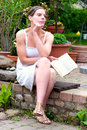 Young woman sitting in garden reading a book white summer dress and Royalty Free Stock Images