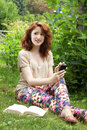 Young woman sitting on grass smiling using a phone and relaxing at park Stock Photos