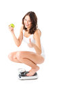 Young woman sitting on her haunches on a scale diet and weight she is happy about the success Stock Photography