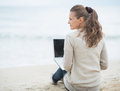 Young woman sitting with laptop on cold beach lonely Royalty Free Stock Images