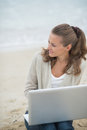 Young woman sitting with laptop on cold beach and looking into distance Stock Image