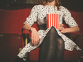 Young woman sitting in movie theater with popcorn Royalty Free Stock Photo