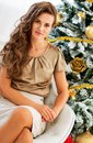 Young woman sitting near christmas tree