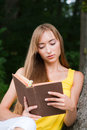 Young woman sitting near a tree,reading a book Royalty Free Stock Photo