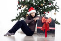 Young woman sitting near xmas tree with present beautiful Stock Photo