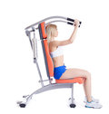 Young woman sitting on orange hydraulic exerciser Stock Image