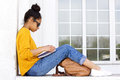 Young woman sitting outdoors and reading a book Royalty Free Stock Photo